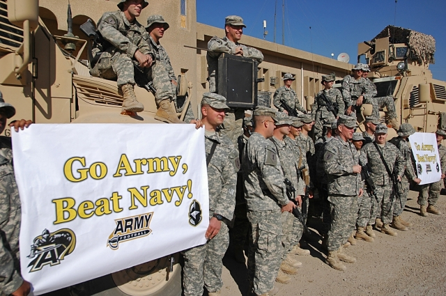 "2011: Col. Ricky D. Gibbs, commander of the 4th Infantry Brigade Combat Team, 1st Inf. Div., and other Dragon Brigade Soldiers show their support for the ""Black Knights"" of the U.S. Military Academy at West Point by shouting out, ""Go Army Beat Navy!"" at Forward Operating Base Falcon in southern Baghdad, Nov. 25. Photo and caption: U.S. Army."