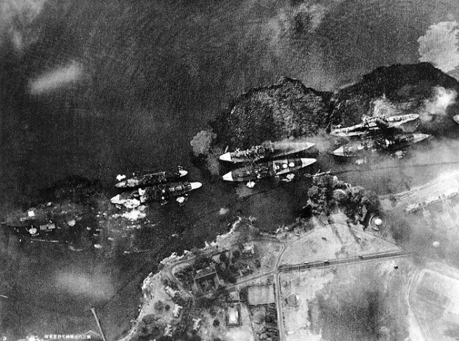 "Vertical aerial view of ""Battleship Row"", beside Ford Island, during the early part of the horizontal bombing attack on the ships moored there. Photographed from a Japanese aircraft. Ships seen are (from left to right): USS Nevada ; USS Arizona with USS Vestal moored outboard; USS Tennessee with USS West Virginia moored outboard; USS Maryland with USS Oklahoma moored outboard; and USS Neosho, only partially visible at the extreme right. A bomb has just hit Arizona near the stern, but she has not yet received the bomb that detonated her forward magazines. West Virginia and Oklahoma are gushing oil from their many torpedo hits and are listing to port. Oklahoma's port deck edge is already under water. Nevada has also been torpedoed. Japanese inscription in lower left states that the photograph has been officially released by the Navy Ministry. Photo and caption: National History & Heritage Command."