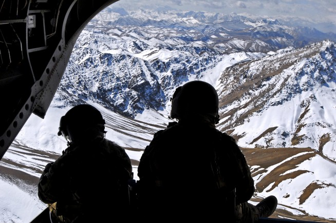 Two crew members keep watch on the rear ramp of a CH-47 Chinook while flying over the mountains in the Khas Uruzgan district of Afghanistan on March 16, 2013. U.S. Army photo by Sgt. Jessi Ann McCormick