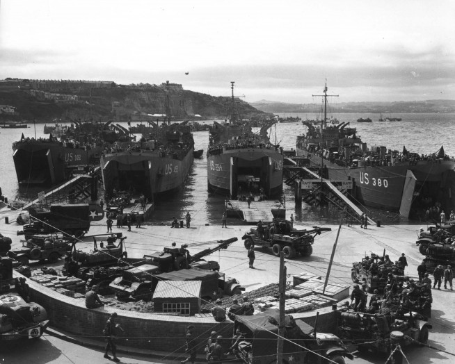 In preparation for the invasion, artillery equipment is loaded aboard LCTS at an English port. Brixham, England. 1 June 1944. Image and caption credit: U.S. Army Center of Military History.