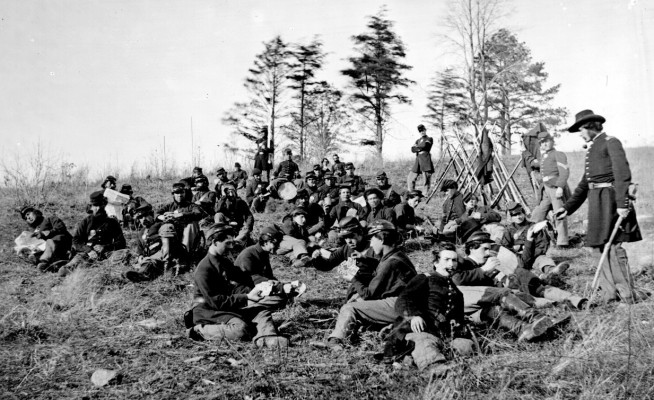 Soldiers at rest after drill, Petersburg, Va., 1864. The soldiers are seated reading letters and papers and playing cards. Image and caption credit: National Archives.