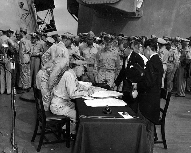 Lieutenant General Richard K. Sutherland, U.S. Army, Chief of Staff to General of the Army Douglas MacArthur, makes corrections to the Japanese copy of the Instrument of Surrender, at the conclusion of surrender ceremonies on board USS Missouri (BB-63), 2 September 1945. Japanese Foreign Ministry representatives Katsuo Okazaki (wearing glasses) and Toshikazu Kase are watching from across the table. Credit: Naval Historical Center.