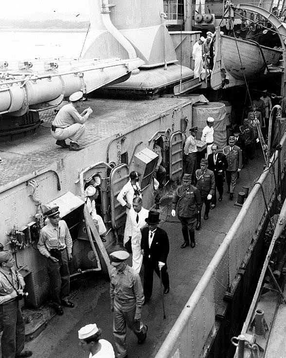 The Japanese representatives follow their escort officer along the deck of USS Lansdowne (DD-486), after the surrender ceremonies. Foreign Minister Mamoru Shigemitsu is leading the delegation, followed by General Yoshijiro Umezu. Credit: Naval Historical Center.