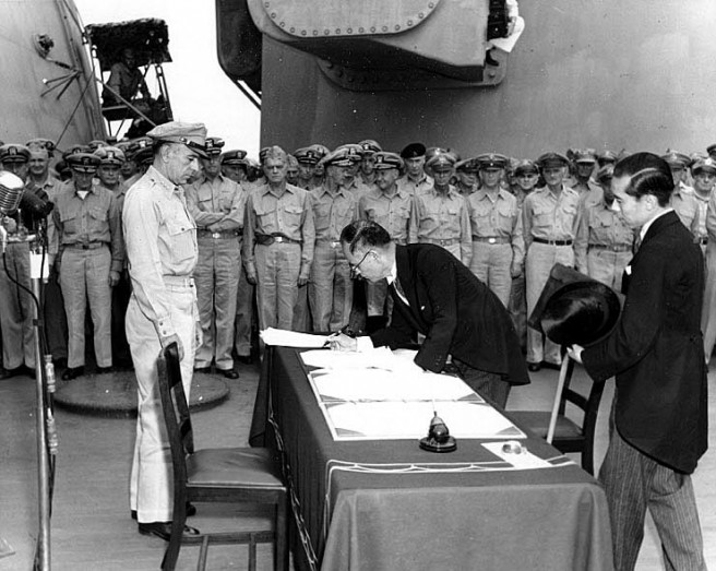 Japanese Foreign Minister Mamoru Shigemitsu signs the Instrument of Surrender on behalf of the Japanese Government, on board USS Missouri (BB-63), 2 September 1945. Lieutentant General Richard K. Sutherland, U.S. Army, watches from the opposite side of the table. Foreign Ministry representative Toshikazu Kase is assisting Mr. Shigemitsu. Credit: Naval Historical Center.