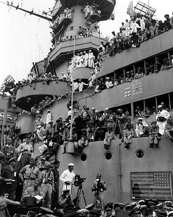 Spectators and photographers crowd USS Missouri's superstructure to witness the formal ceremonies marking Japan's surrender, 2 September 1945. The framed flag in lower right is that hoisted by Commodore Matthew C. Perry on 14 July 1853, in Yedo (Tokyo) Bay, on his first expedition to negotiate the opening of Japan. It had been brought from its permanent home in Memorial Hall at the U.S. Naval Academy for use during the surrender ceremonies. Credit: Naval Historical Center.