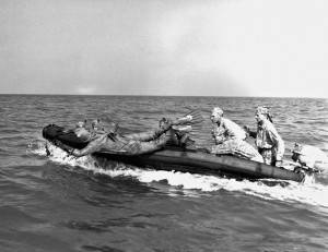 Clad in a rubber exposure suit, a Marine scout swimmer dives from an inflatable boat more than five hundred yards offshore. The exposure suit is worn in cold climates where water temperatures hamper swimmers. Working in teams of two, the scout swimmers examine the beach for obstacles and enemy patrols. If the area is clear, they signal the remainder of the reconnaissance patrol to come ashore. Caption credit: MARSOC by Fred Pushies. Image credit: USMC HISTORY DIVISION, QUANTICO.